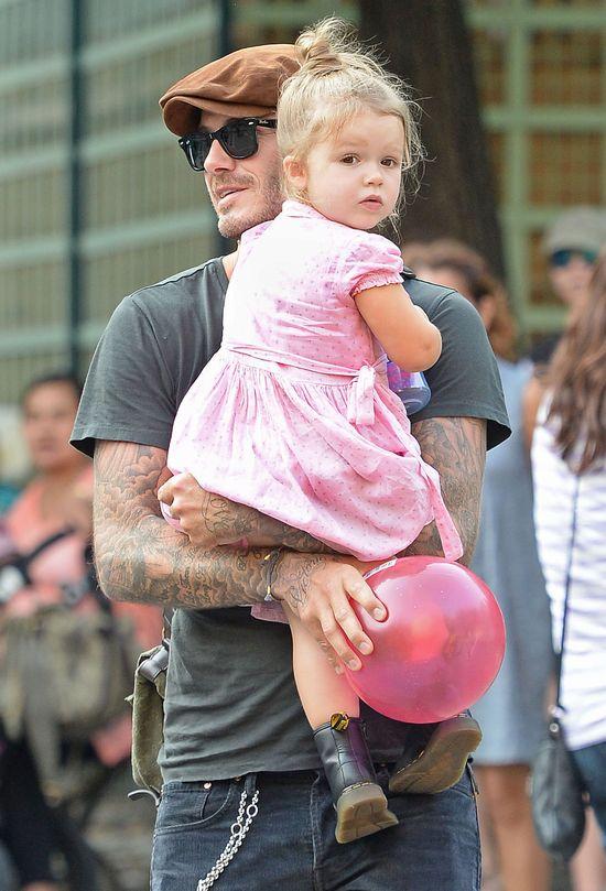 Harper Beckham w różowej sukience w ramionach taty