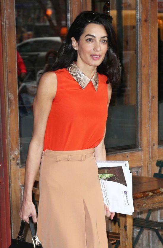 Amal Clooneybw pomarańczowej bluzce z błyszczącym kołnierzykiem i beżowej spódnicy