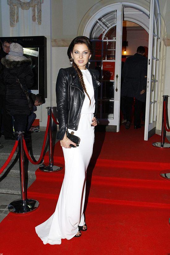 Anna Lewandowska w długiej białej sukni i skórzanej kurtce.