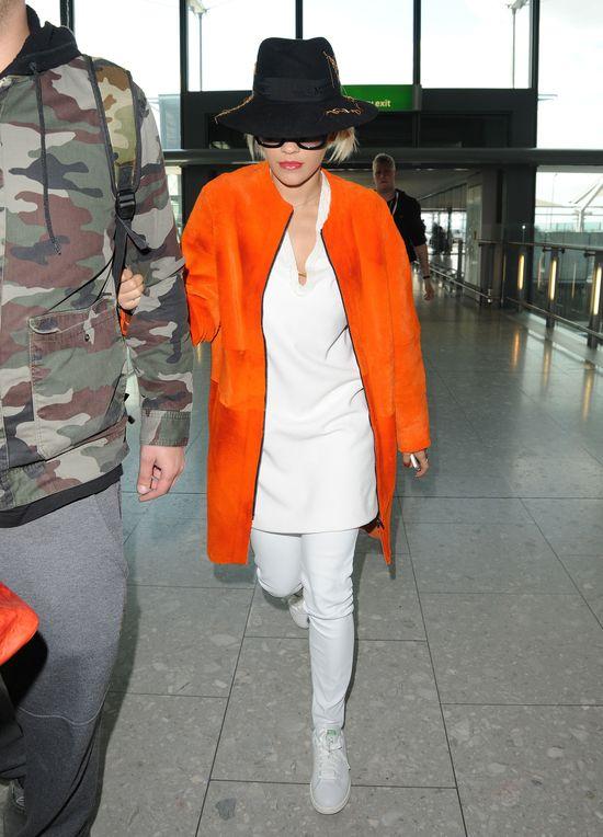 Rita Ora w pomarańczowym płaszczu i białych spodniach i bluzce