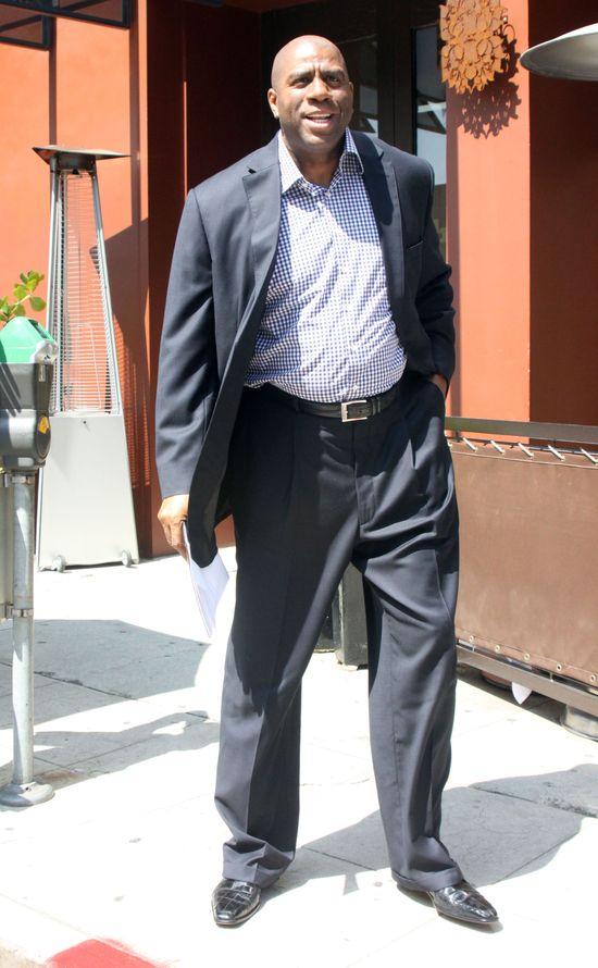 Syn Magica Johnsona w wysokich SZPILKACH przegina się przed restauracją
