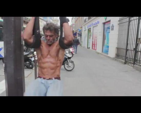 Bezdomny urządził sobie siłownię na paryskiej ulicy [VIDEO]