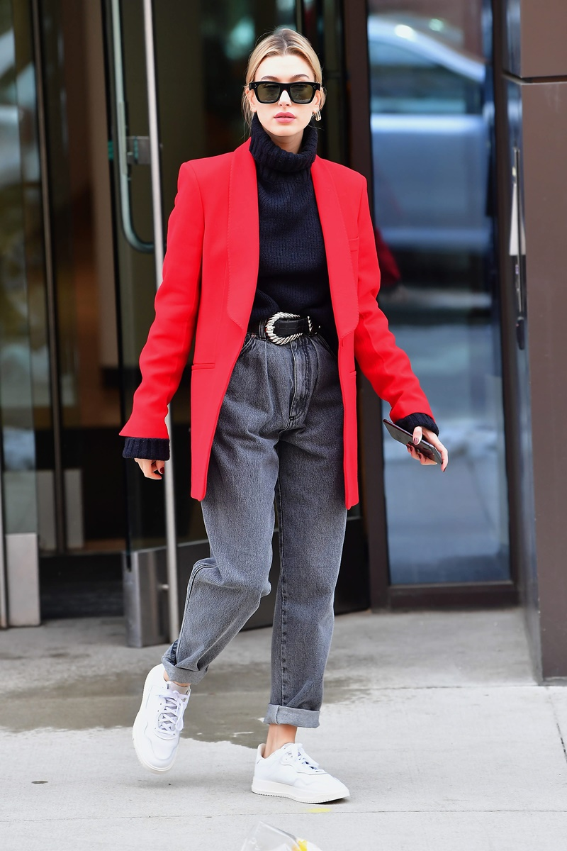 Elegant Hailey Bieber wearing a bright red jacket and adidas sneakers bringing coffee for Justin Bieber