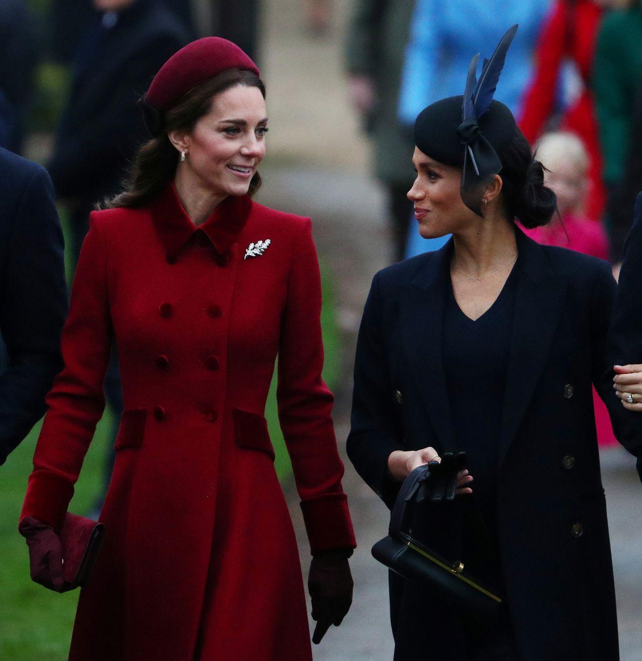 Meghan Markle i księżna Kate patrzą na siebie i uśmiechają
