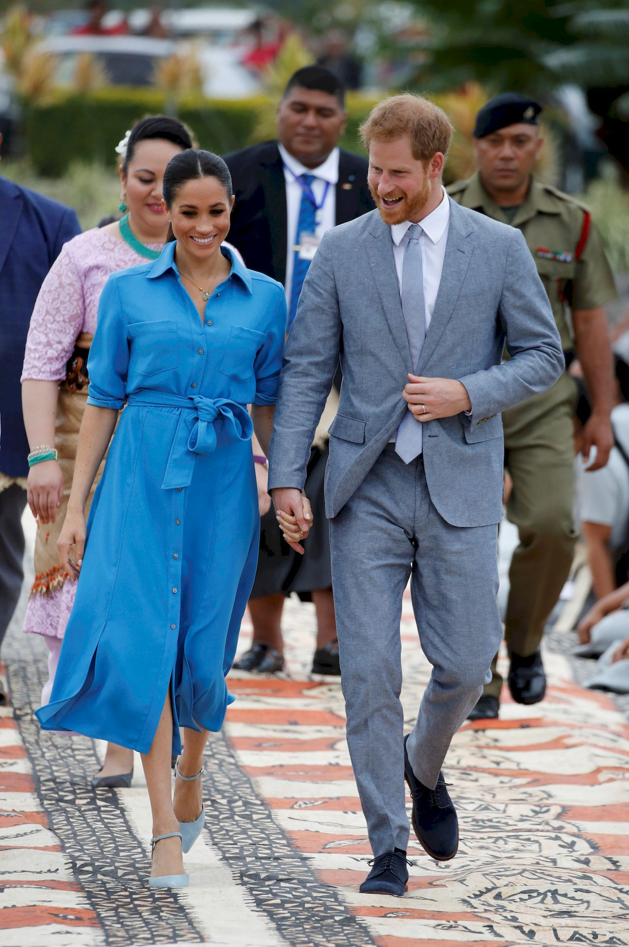 Britain's Prince Harry and Meghan, Duchess of Sussex walk together, ahead of Tonga's Princess Angelika, as they depart from Fua'amotu International Airport in Tonga