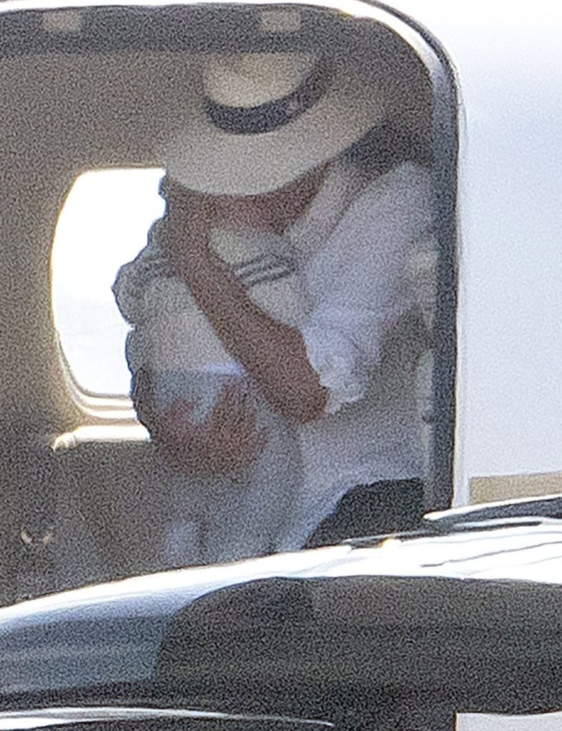 *PREMIUM EXCLUSIVE NO WEB UNTIL 2230 BST 18TH AUG* Meghan Markle cradles baby son Archie in both arms as she leaves the luxury private jet she and Prince Harry have come under fire for using while claiming to be eco warriors.
