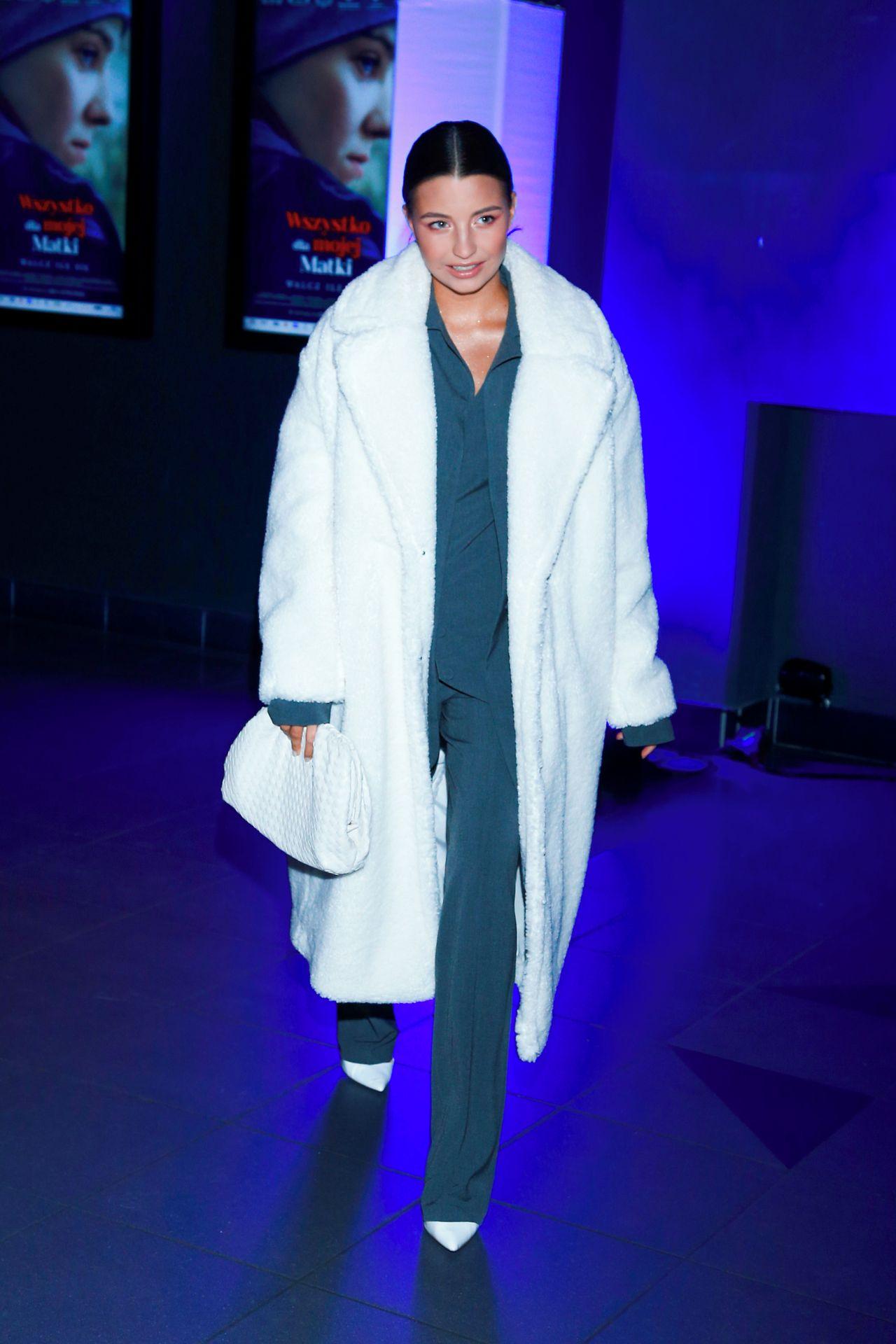 Elegancka Julia Wieniawa w garniturze i obszernym płaszczu.