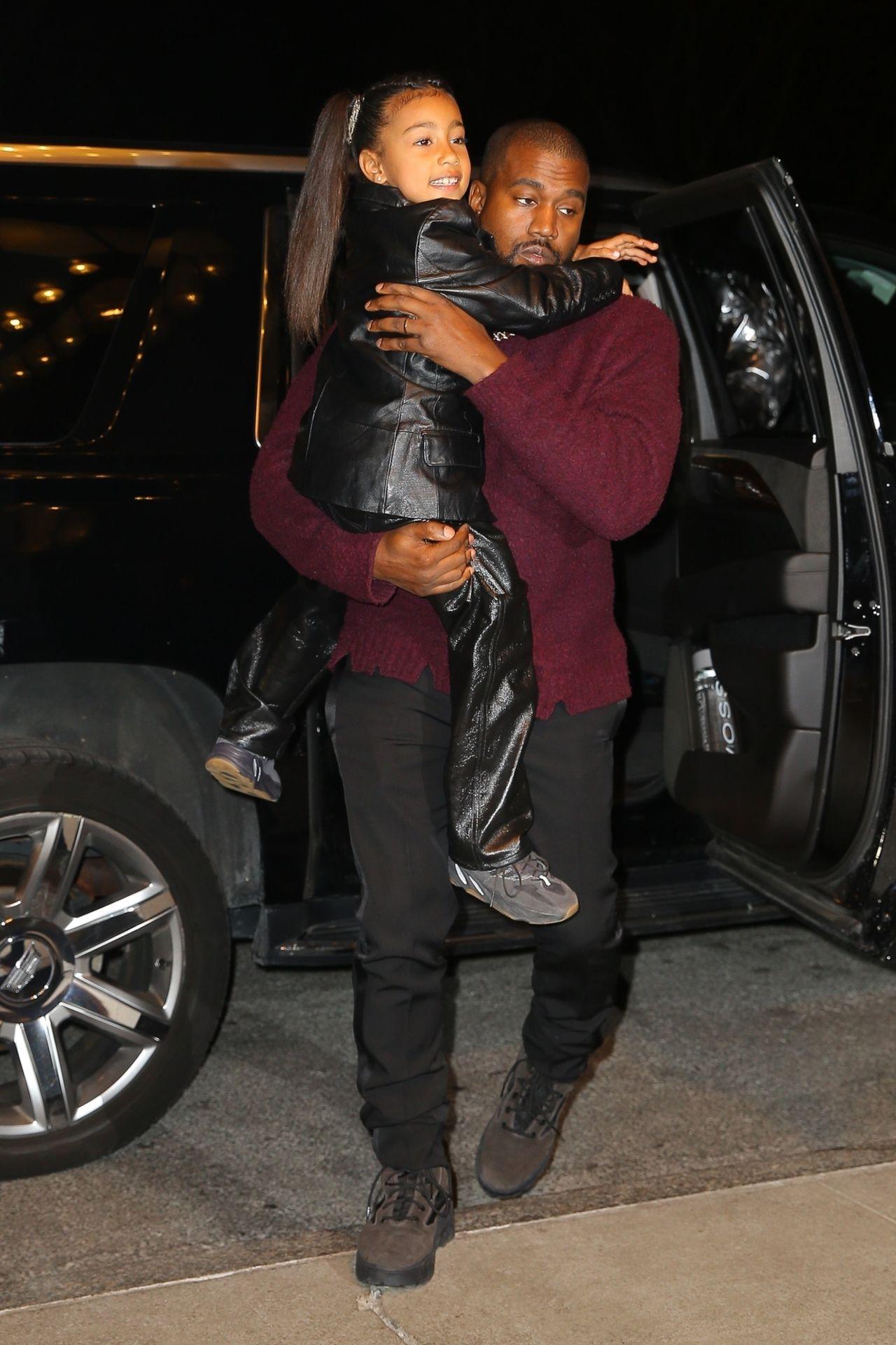 Kanye West trzyma córkę North na rękach.