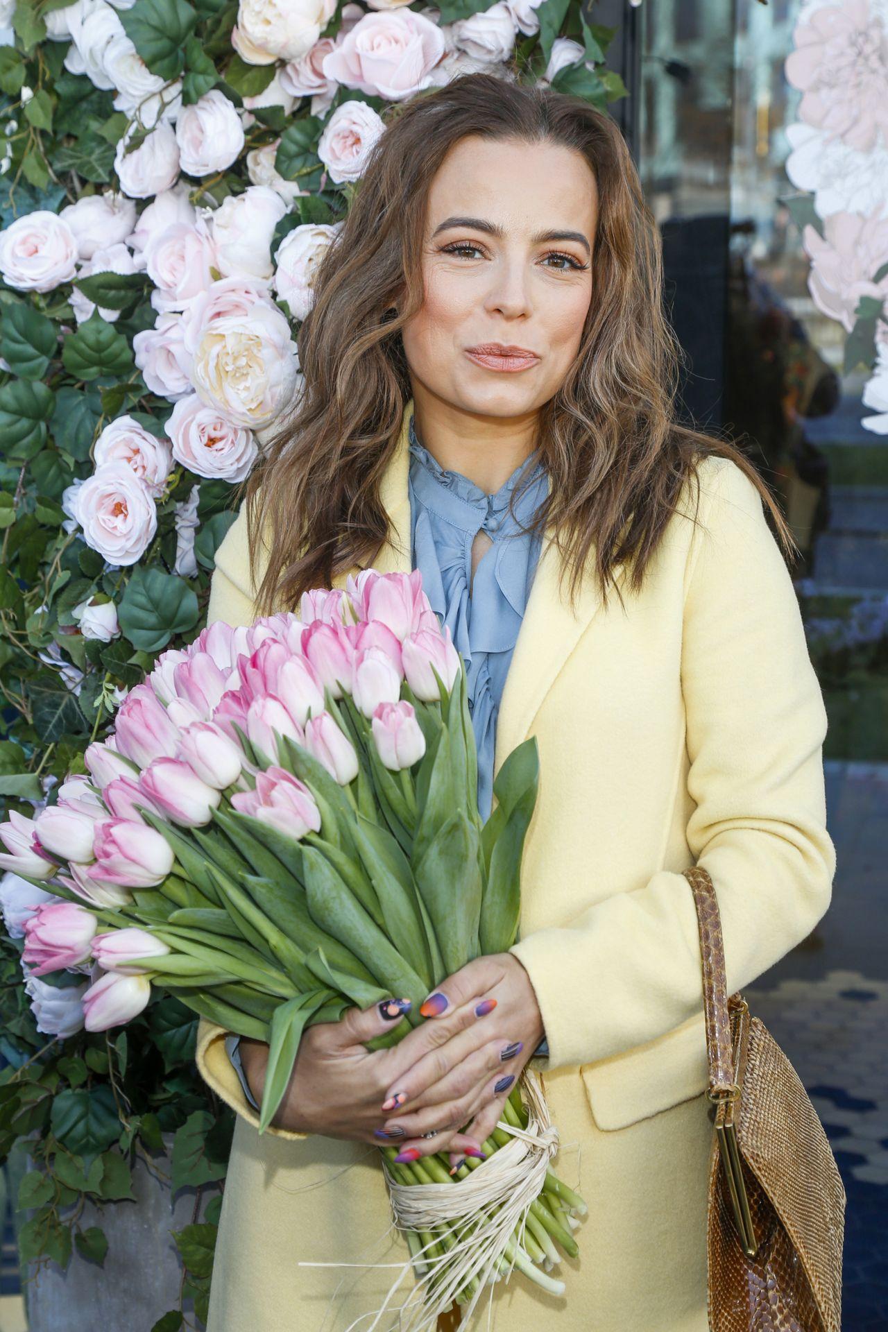 Anna Mucha pozuje z bukietem kwiatów.