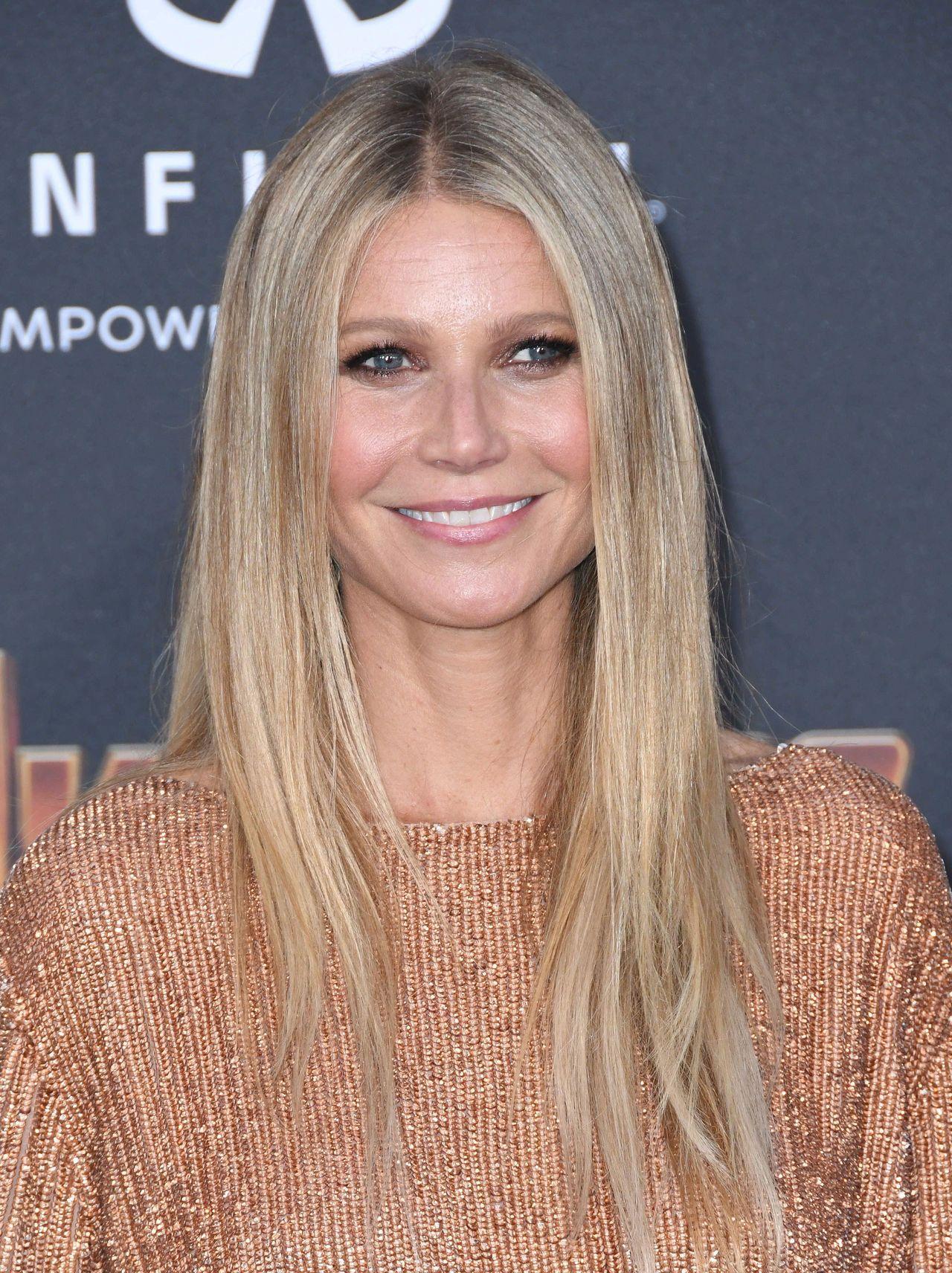 Promienna Gwyneth Paltrow w złotej sukience na ściance.