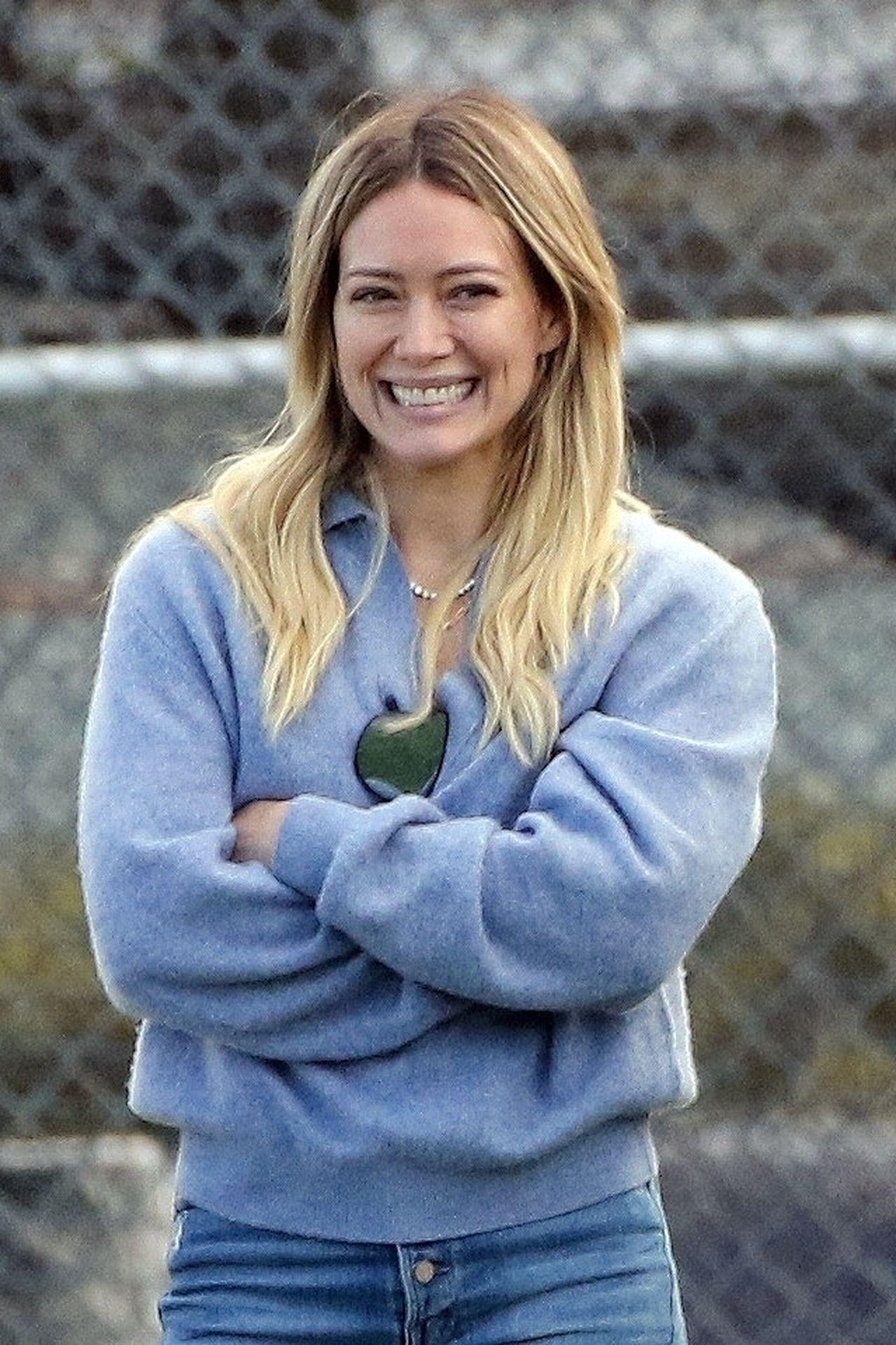 Uśmiechnięta Hilary Duff w szarej bluzie.