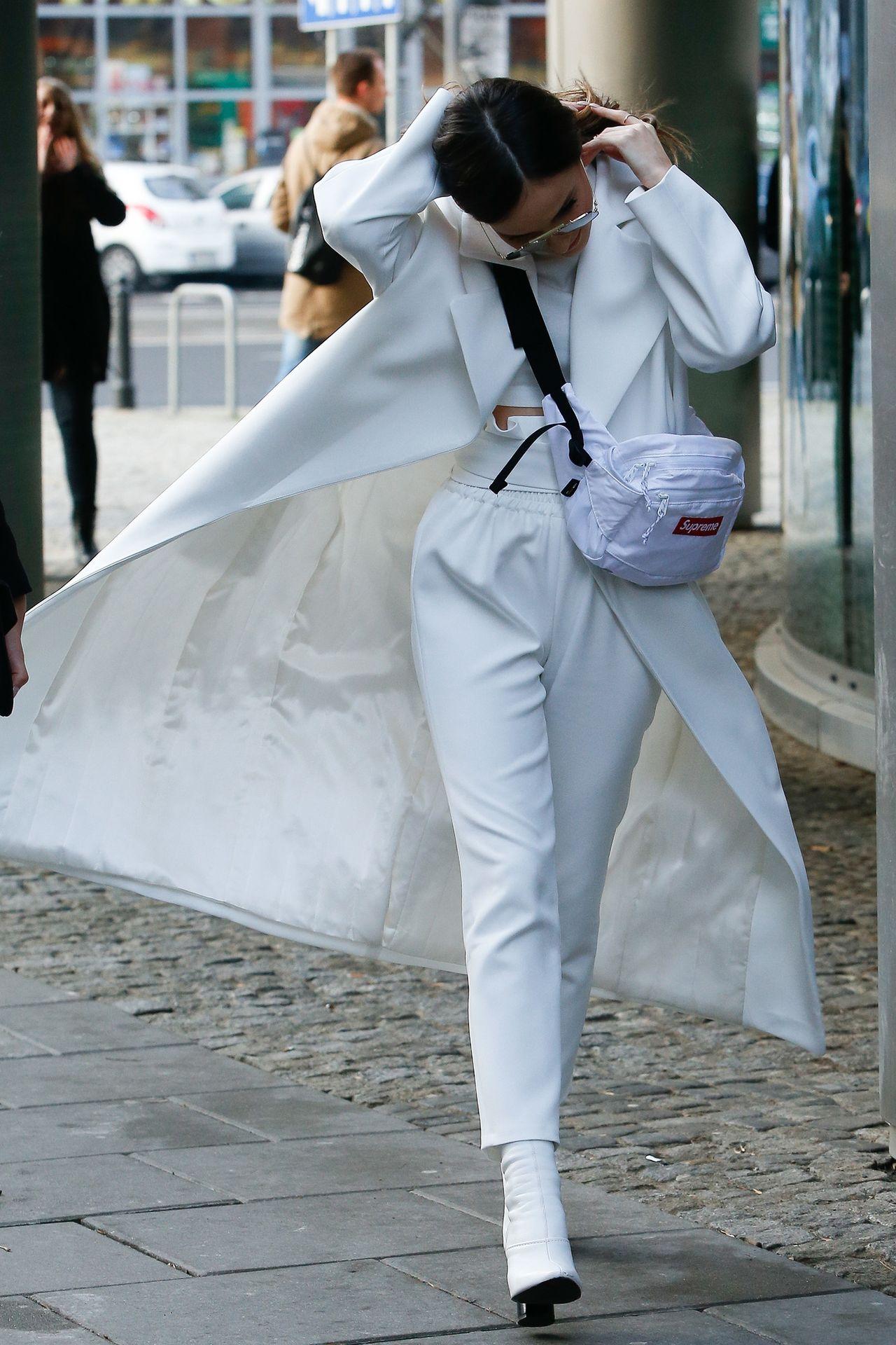 Marina Łuczenko-Szczęsna cała na biało wychodzi ze studia telewizyjnego.