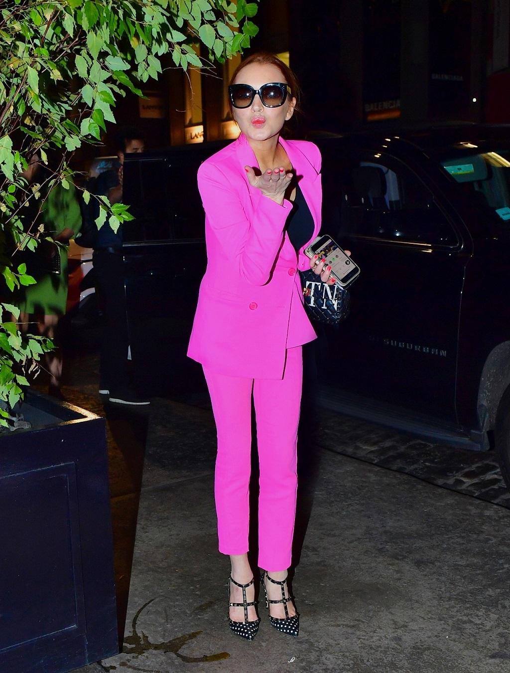 Lindsay Lohan w różowym garniturze przesyła całusa fotoreporterom.
