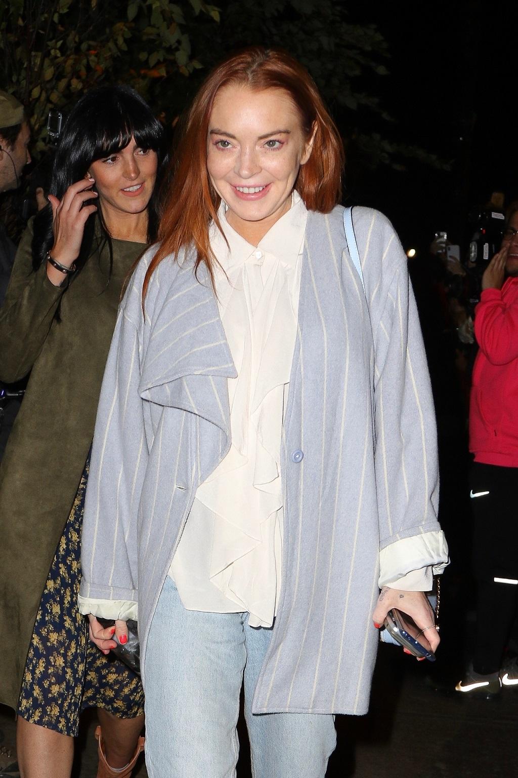 Lindsay Lohan przerażająco się uśmiecha w stronę fotoreporterów.