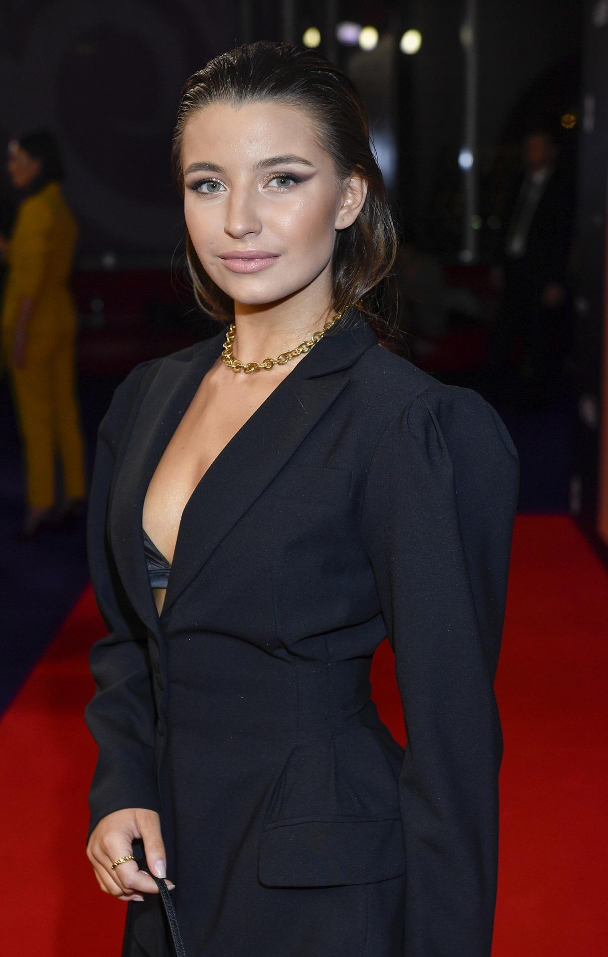 Julia Wieniawa w czarnym garniturze świeci stanikiem na czerwonym dywanie.