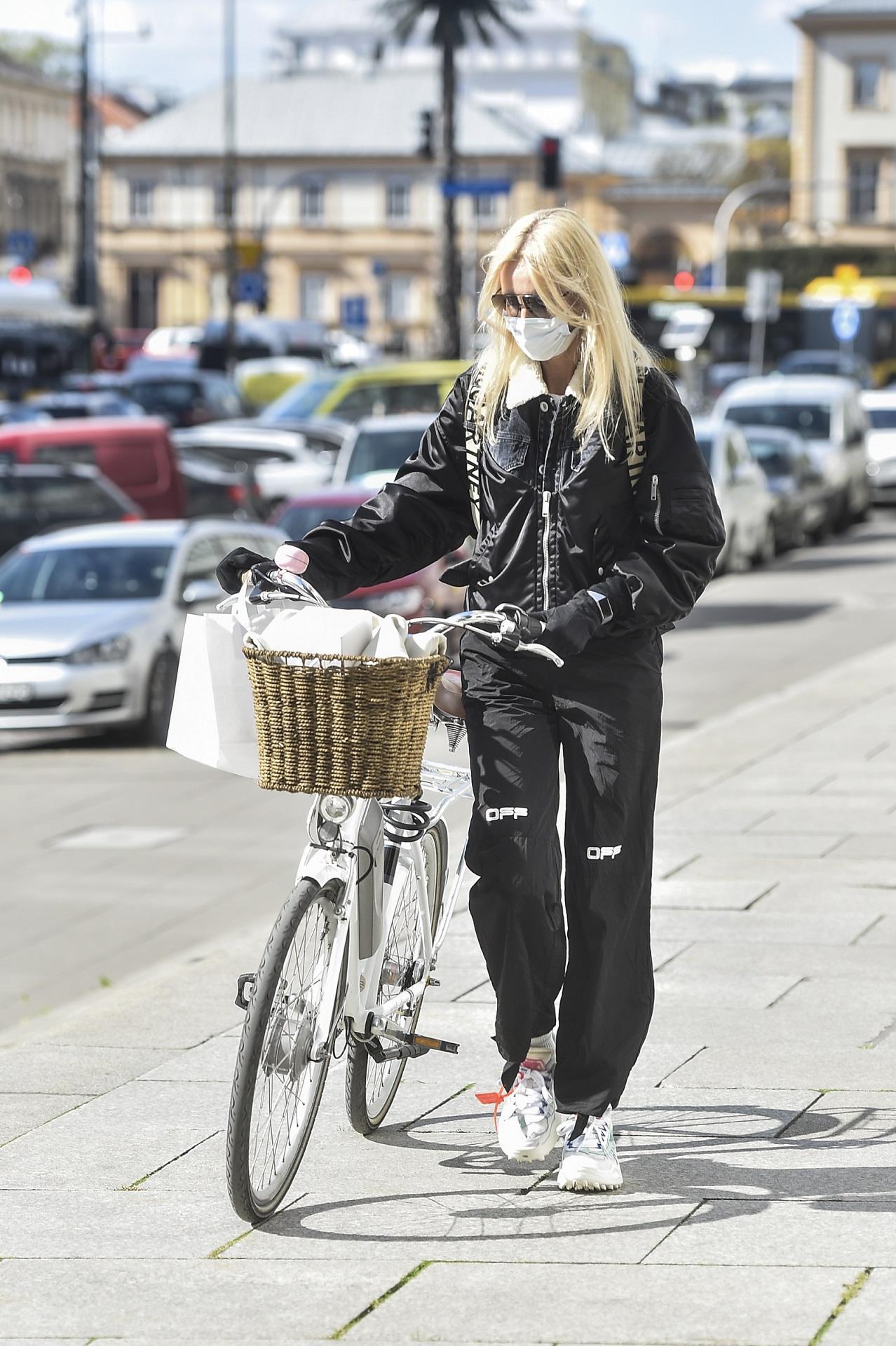 Agnieszka Woźniak-Starak prowadzi rower.