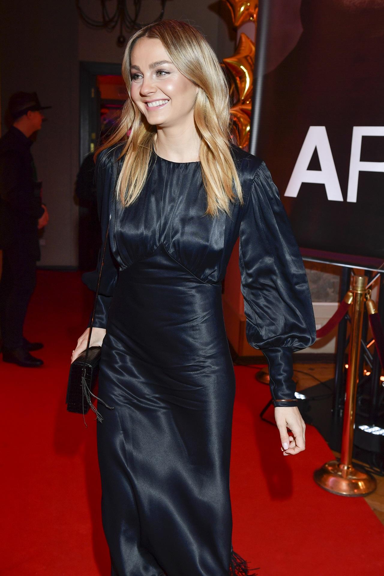 Małgorzata Socha w eleganckiej, czarnej sukni na czerwonym dywanie.