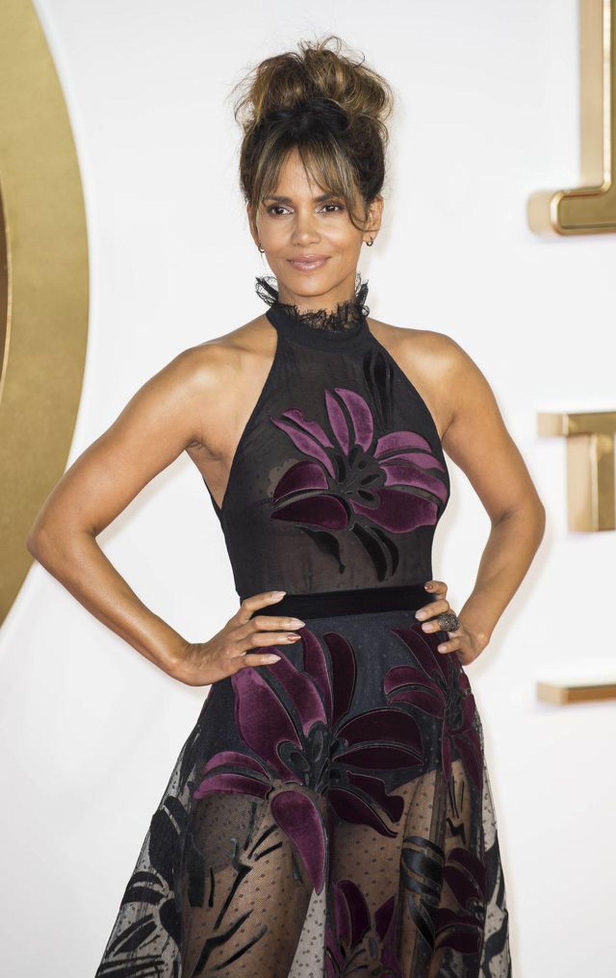 Halle Berry w czarnej sukience z prześwitującym dołem pozuje na ściance.