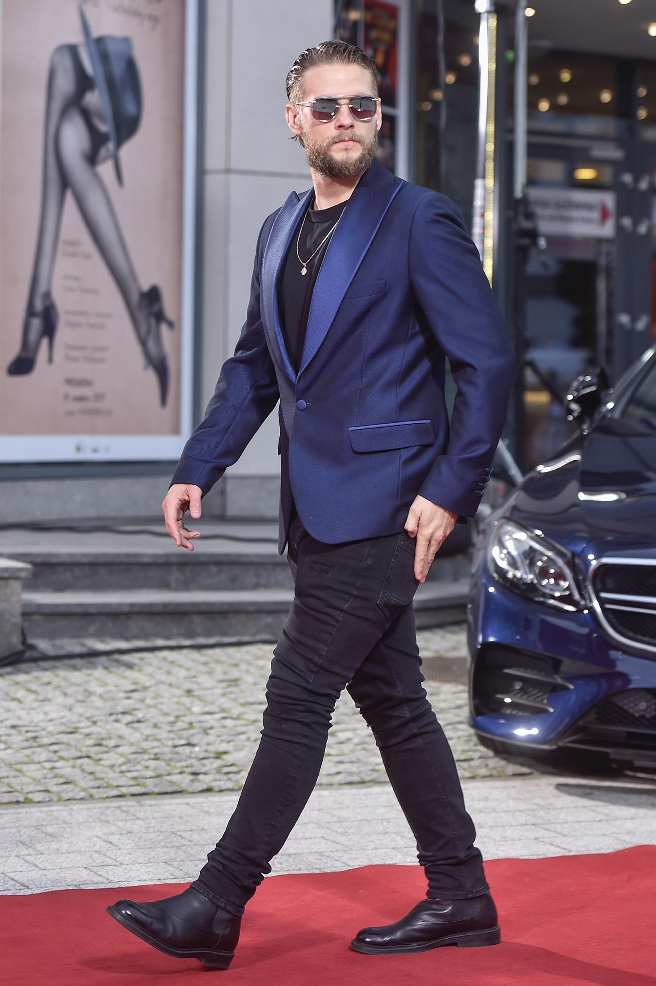 Sebastian Fabijański w eleganckim garniturze na czerwonym dywanie.
