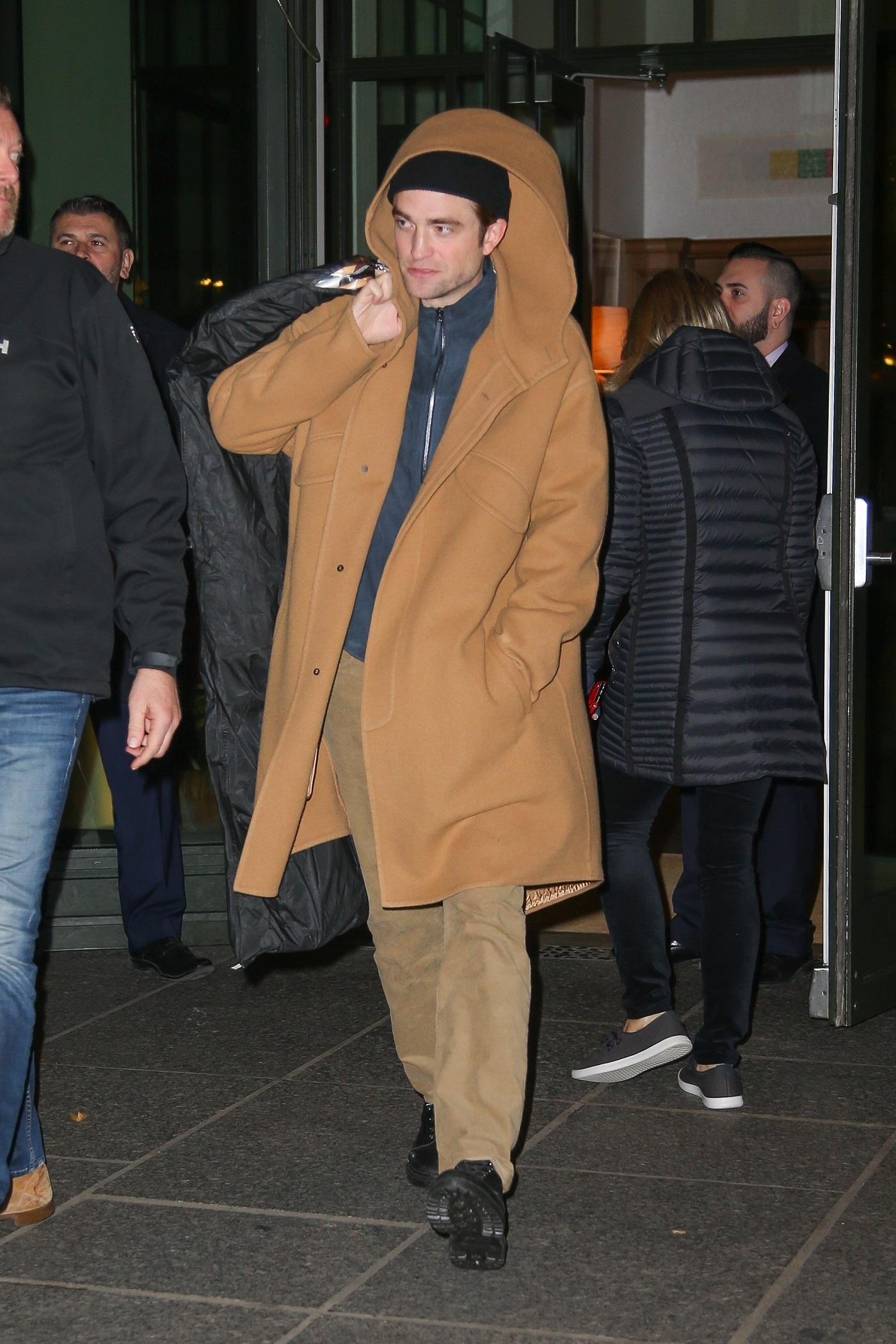 """Robert Pattinson jak Edward ze """"Zmierzchu"""" w modnym płaszczu wychodzi z hotelu."""