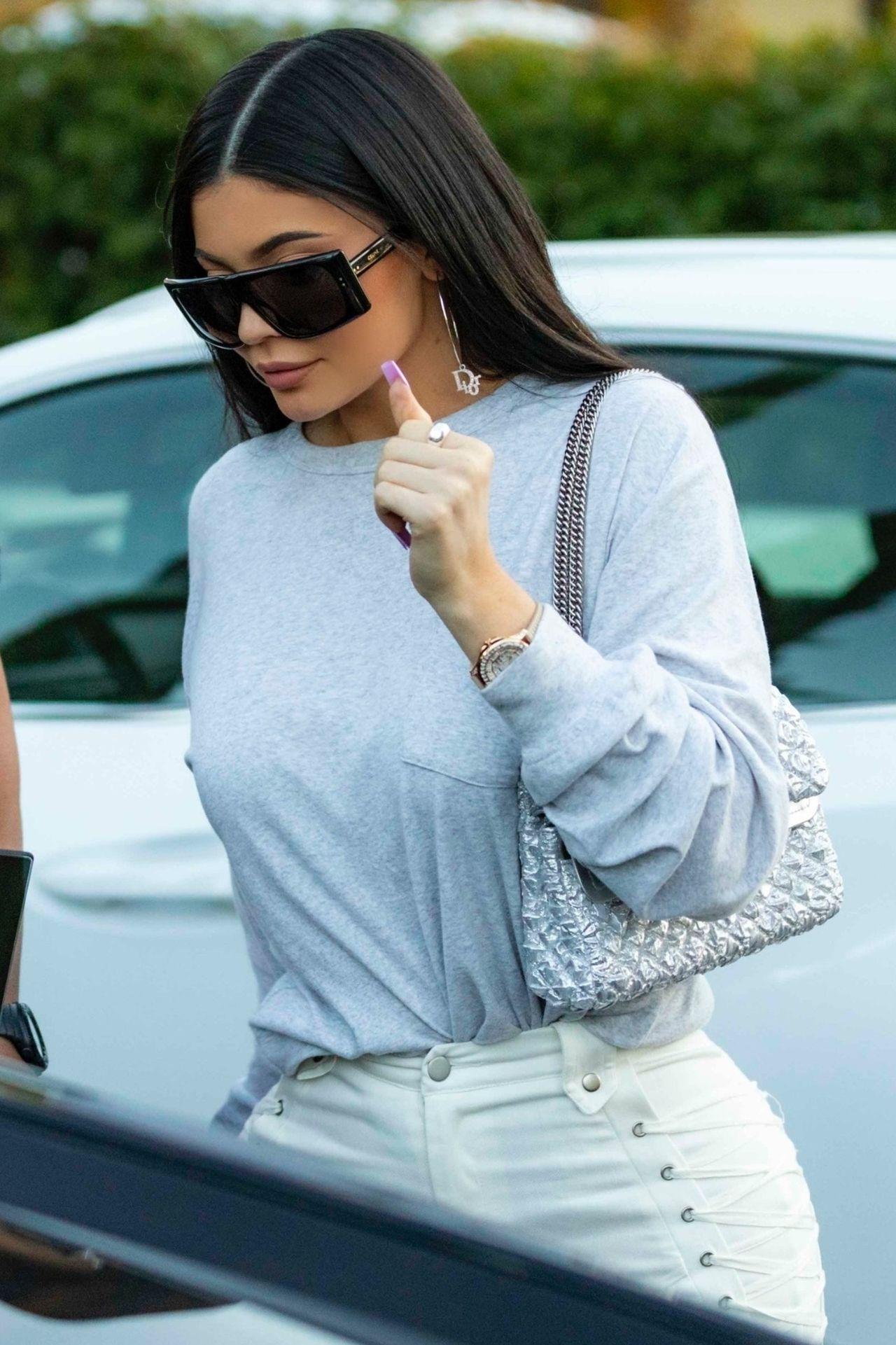 Kylie Jenner w szarej bluzie i okularach przeciwsłonecznych