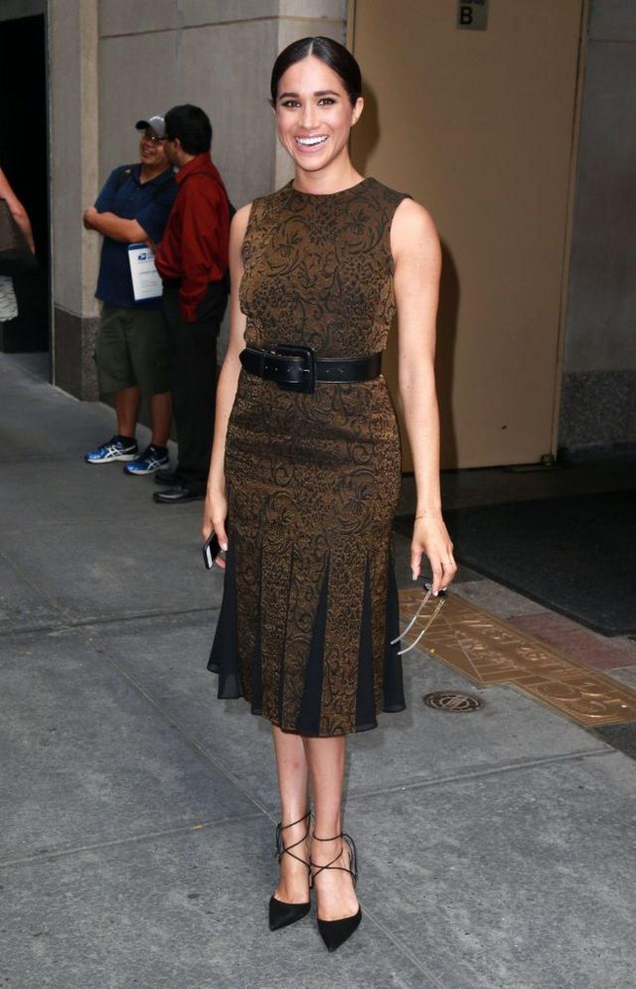Szczęśliwa Meghan Markle w eleganckiej sukience pozuje przed fotoreporterami.