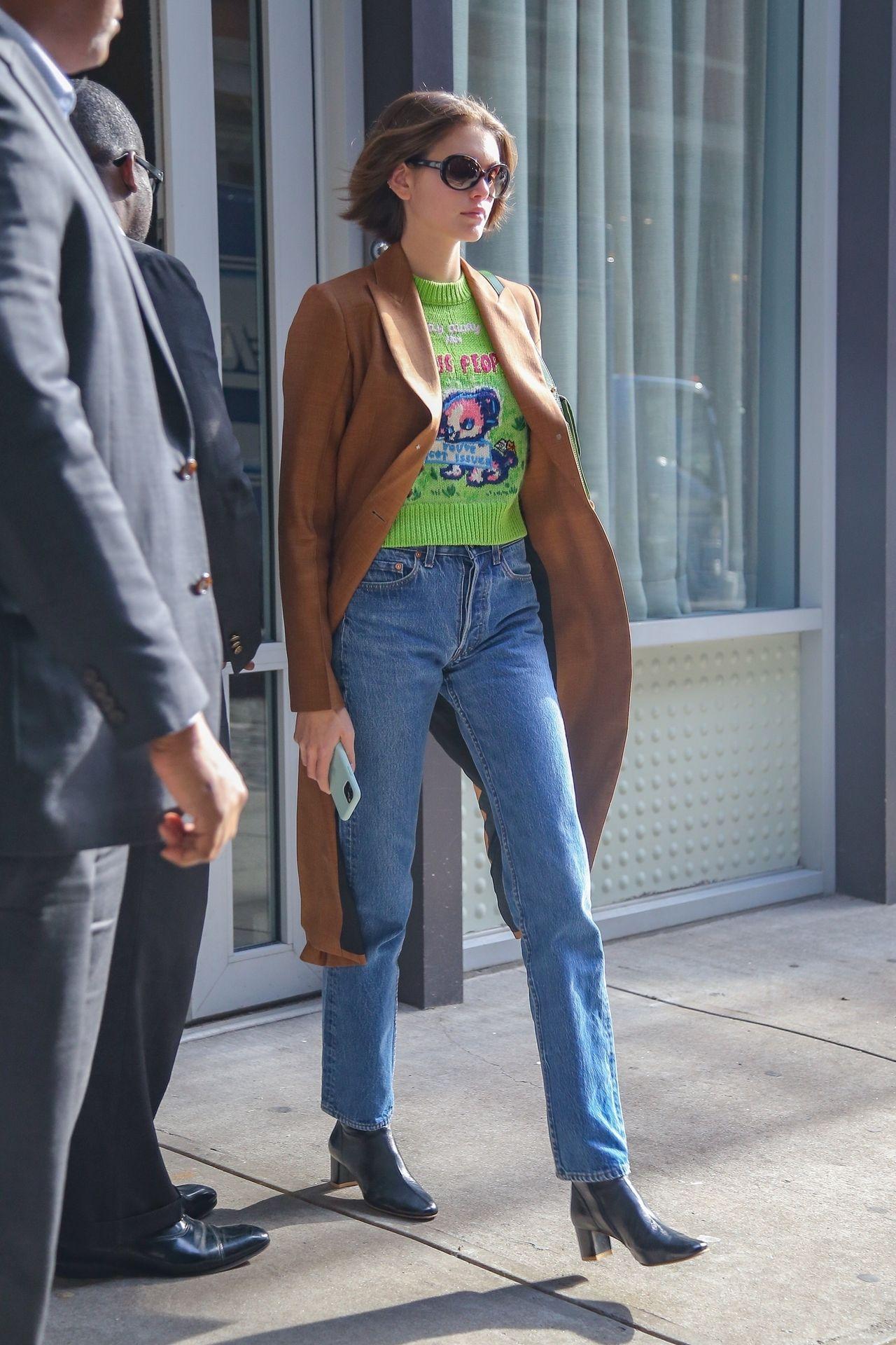 Kaia Gerber w zielonym swetrze i camelowym płaszczu przyłapana przez fotoreporterów.