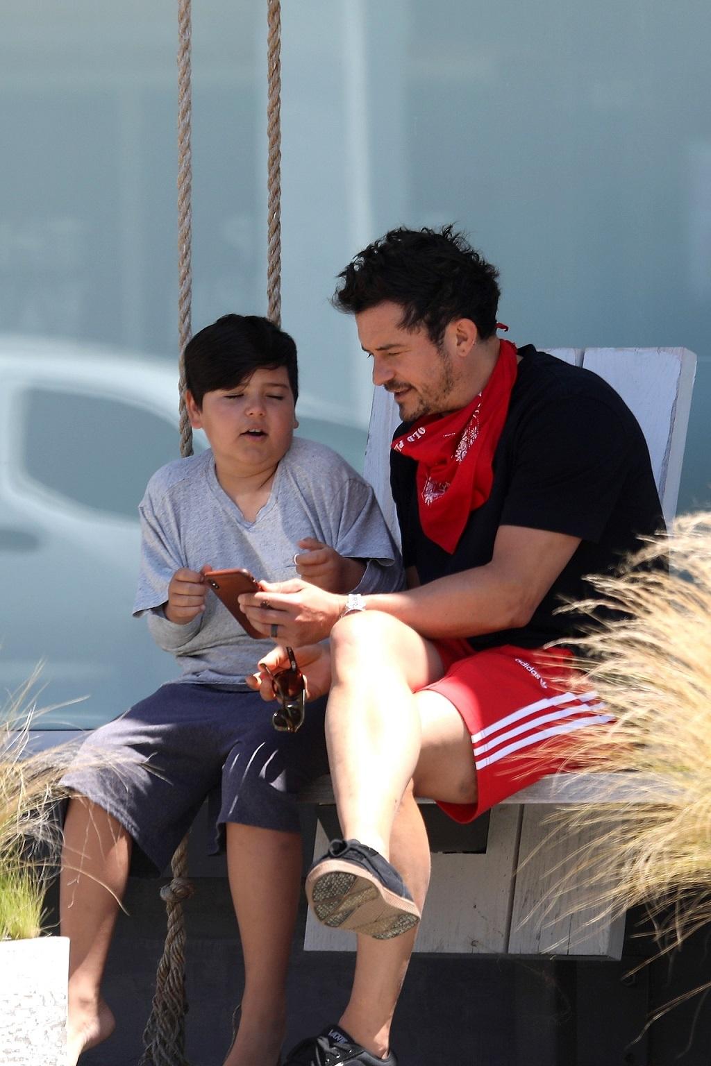 Orlando Bloom z synem ogląda coś na telefonie.