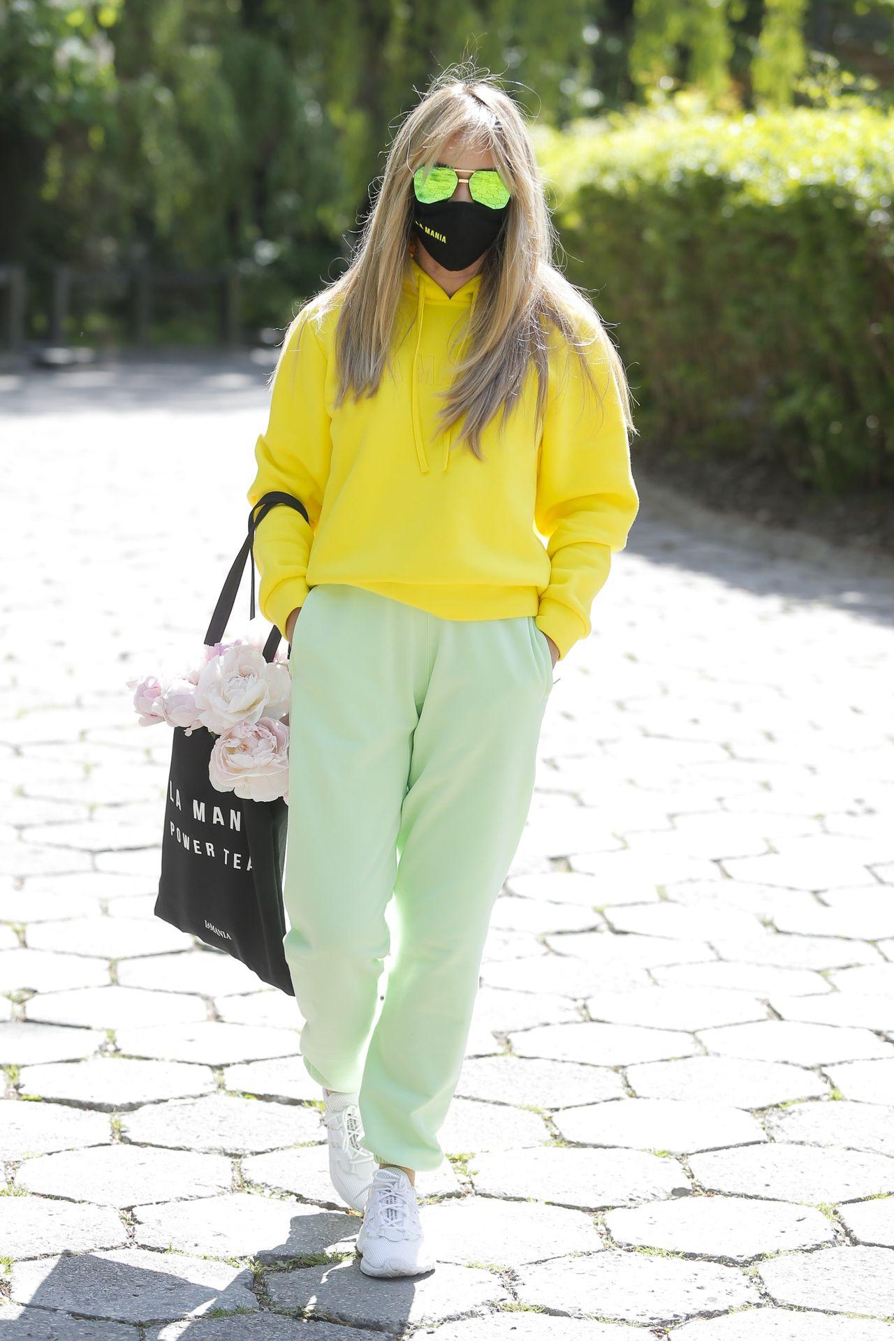 Joanna Przetakiewicz w maseczce i żółtej bluzie.