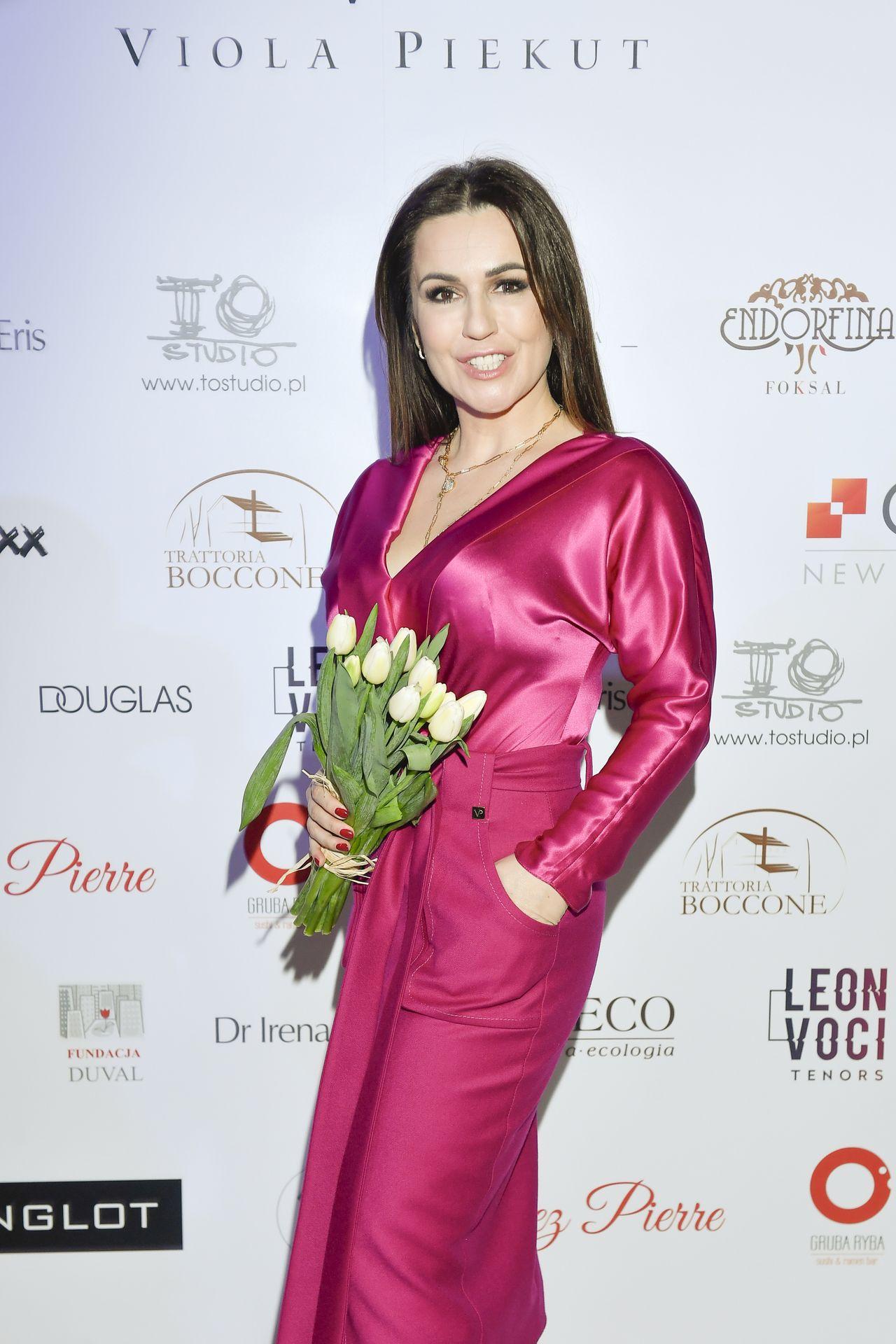Beata Tadla w eleganckiej sukience na ściance.
