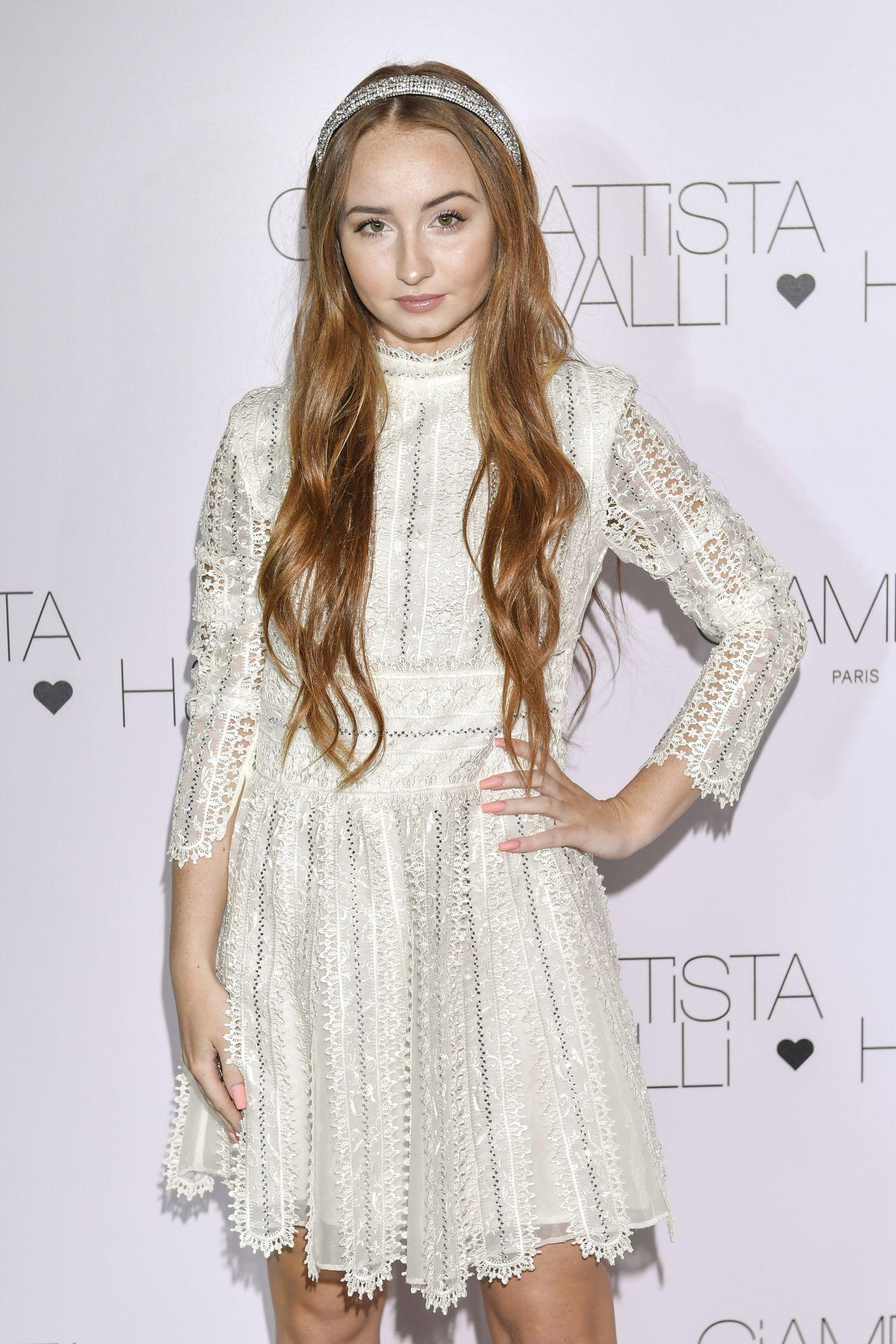 Angelika Mucha w białej,d dziewczęcej sukience na ściance.