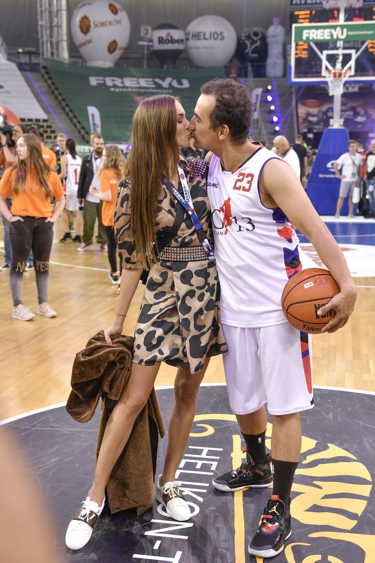 Marcela Leszczak i Michał Koterski całują się na meczu koszykówki.