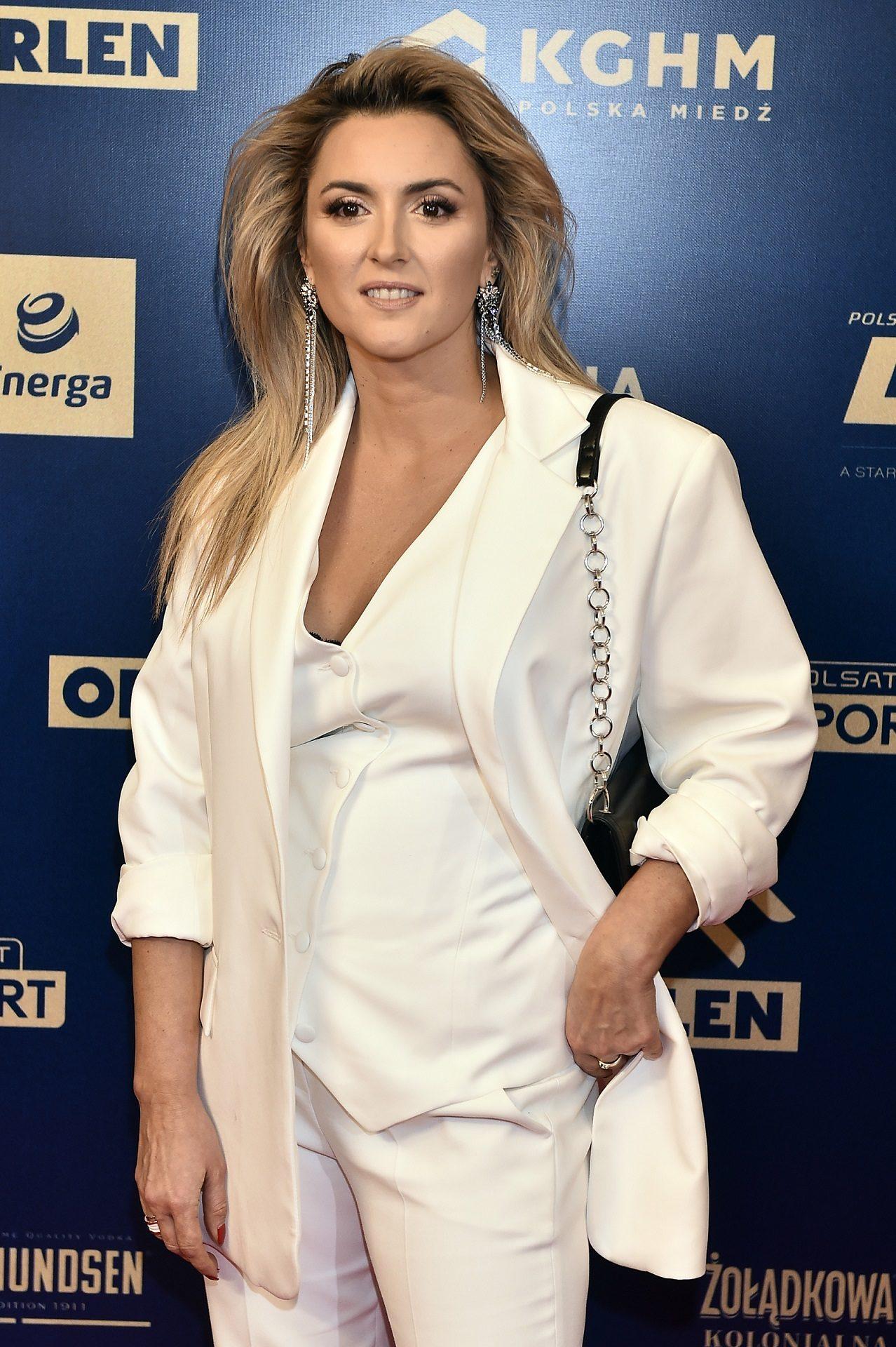 Karolina Szostak w białej stylizacji pozuje na ściance.