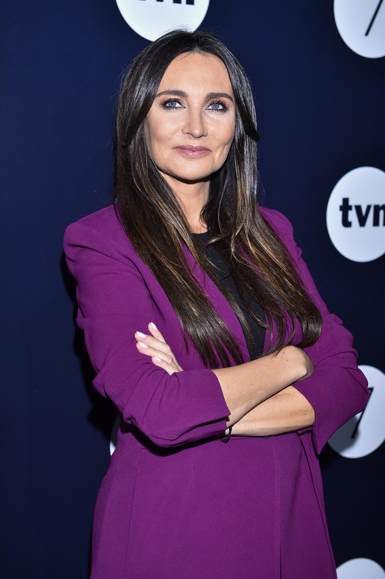 Dominika Kulczyk w fioletowym zestawie pozuje na ściance.