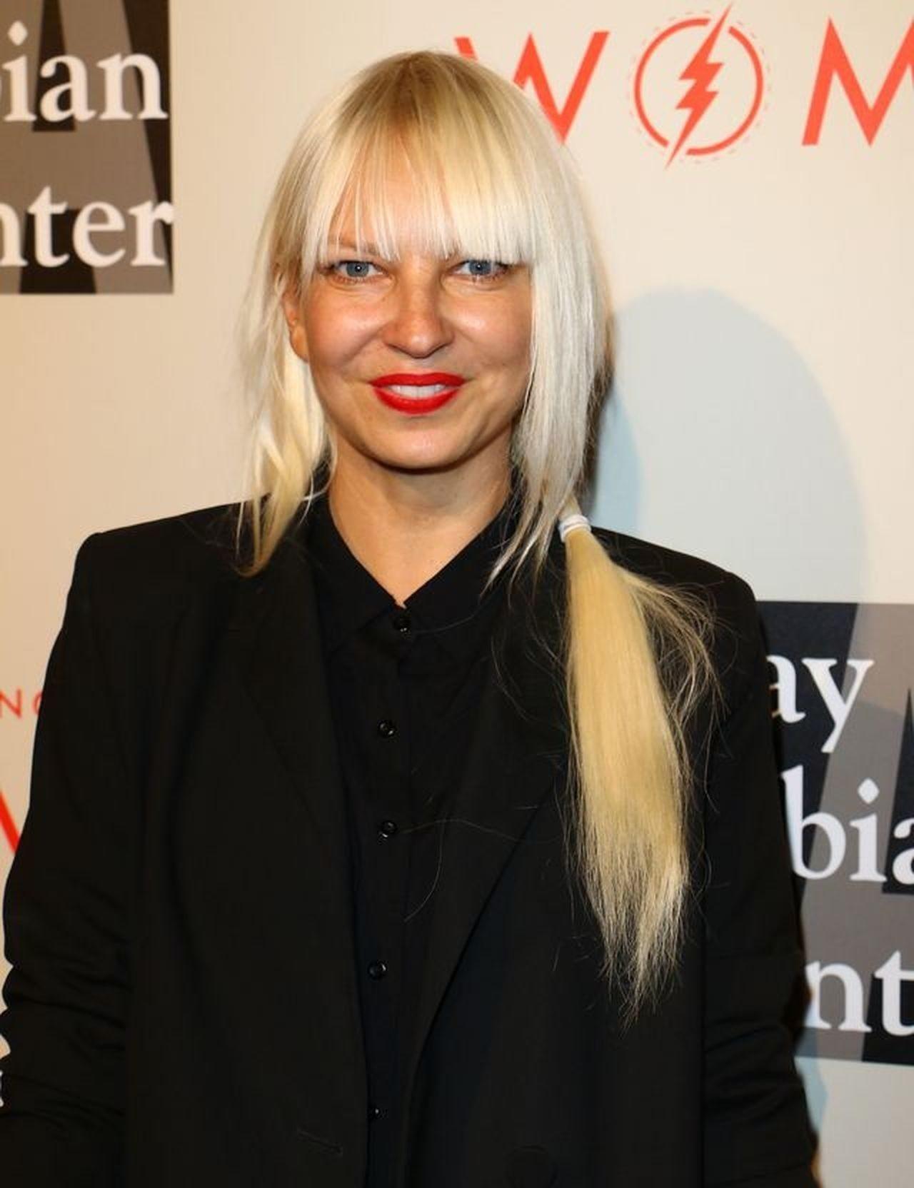 Wokalistka Sia pozuje na ściance bez peruki zasłaniające twarz.
