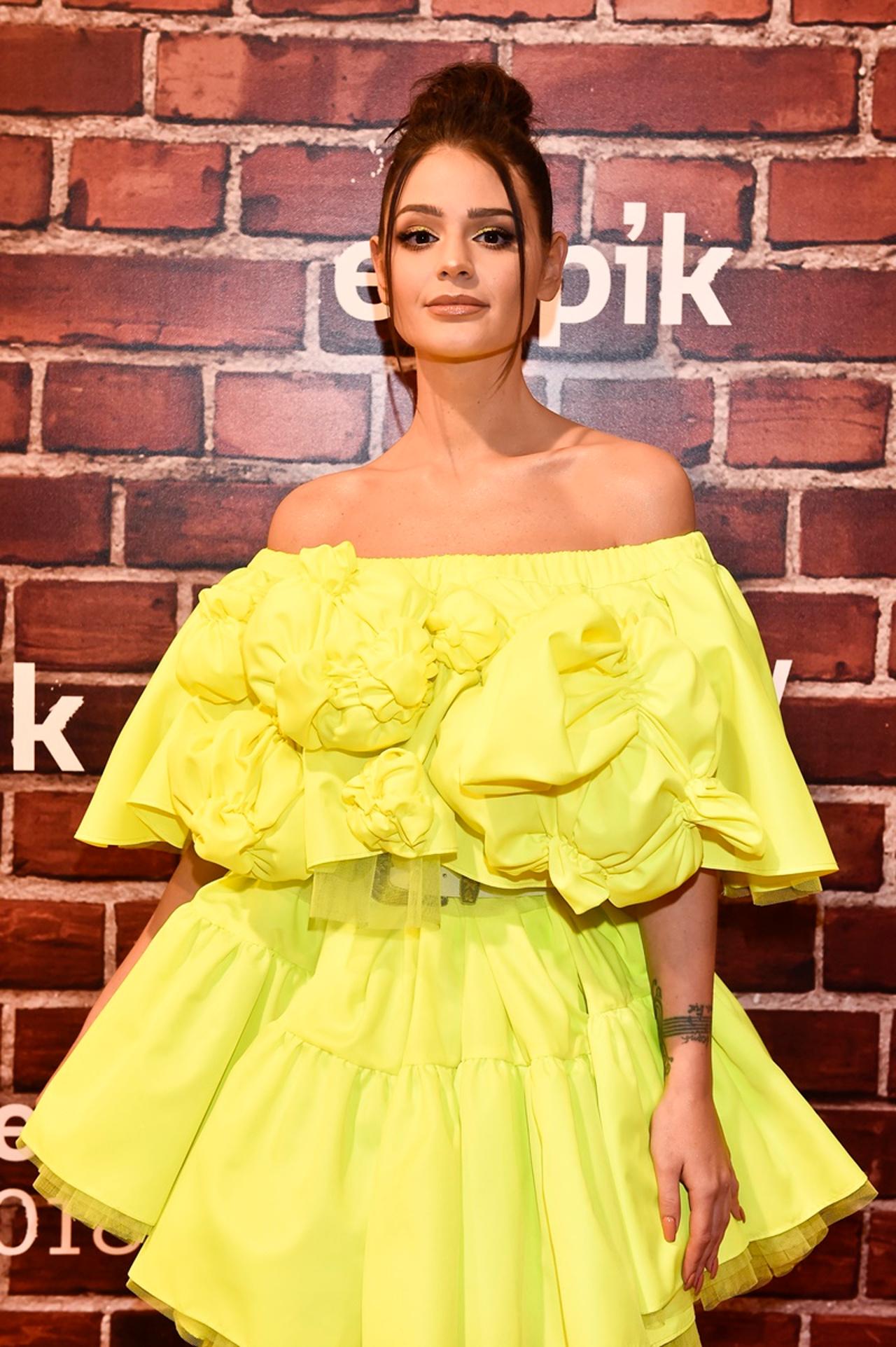 Honorata Skarbek w żółtej sukience na ściance.