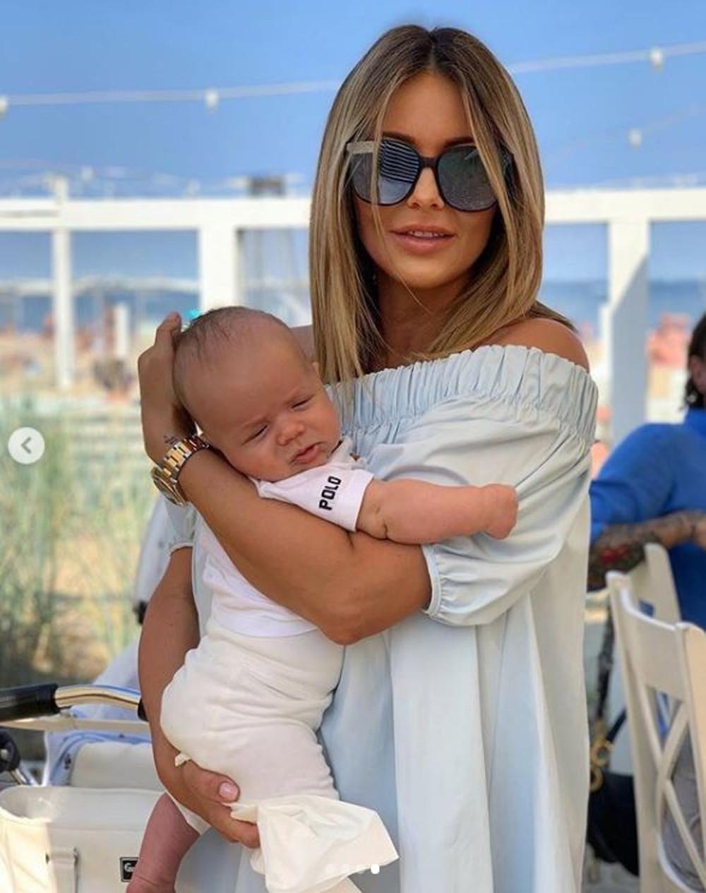 Małgorzata Rozenek w letniej stylizacji trzyma syna Henryka na rękach.