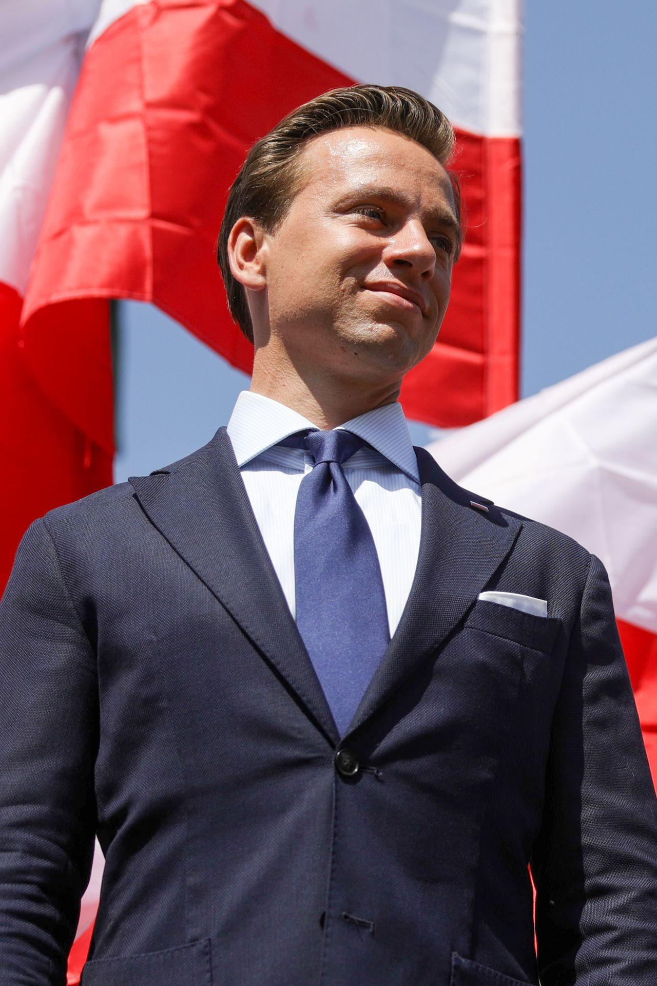 Krzysztof Bosak na tle flagi Polski