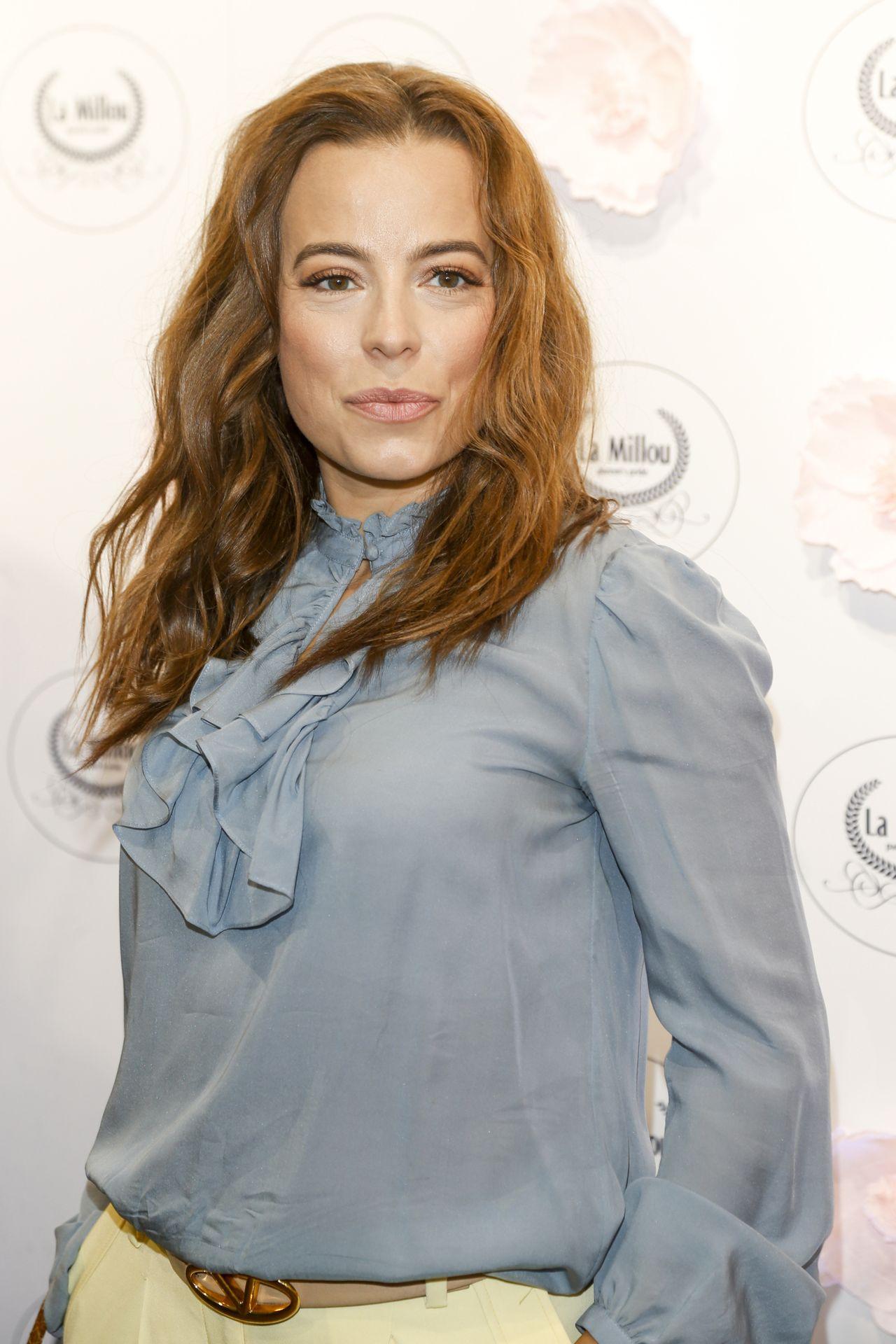 Anna Mucha w niebieskiej koszuli na ściance.