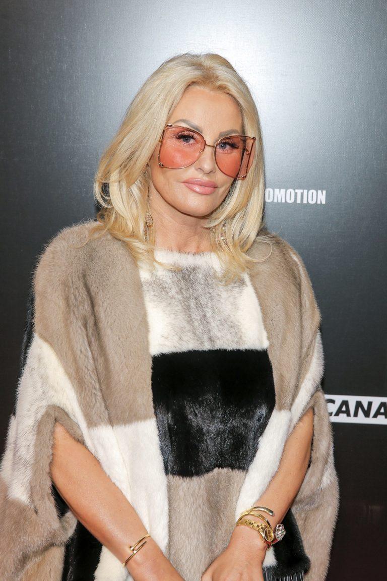 Dagmara Kaźmierska w futrze i okularach na czerwonym dywanie.