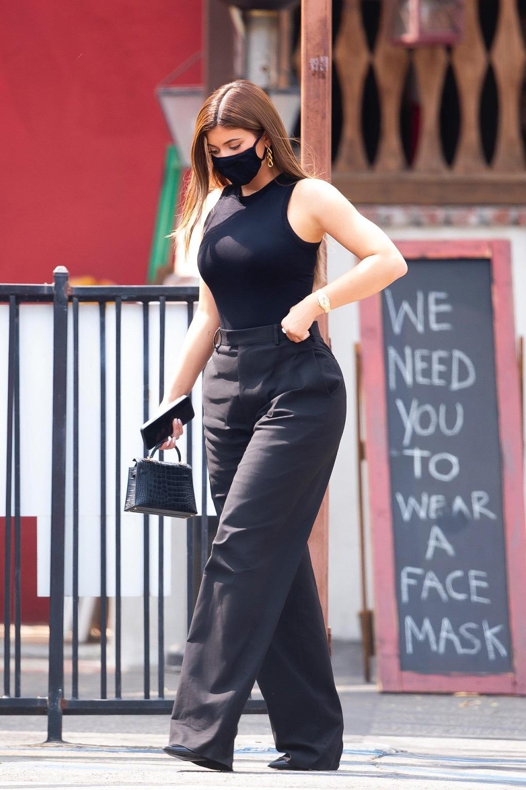 Kylie Jenner cała na czarno w maseczce na twarzy.