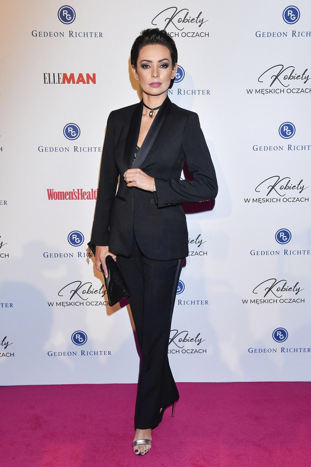 Dorota Gardias w czarnym garniturze na ściance.