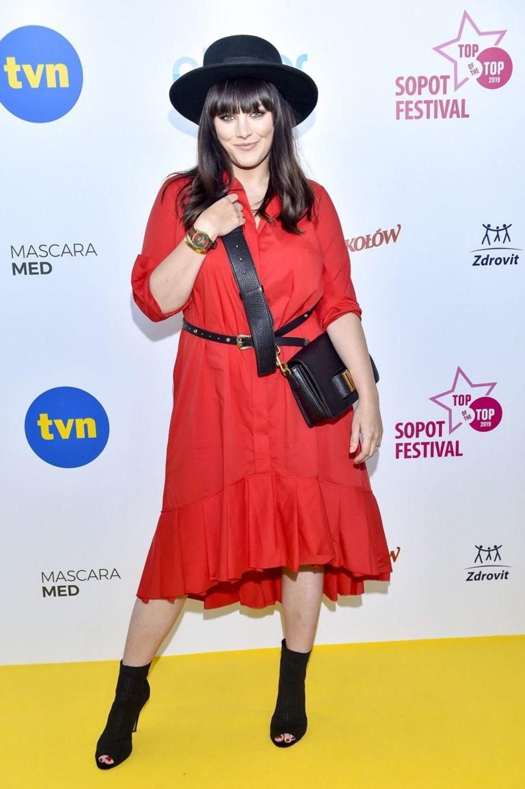 Ewa Farna w czerwonej sukience na ściance.