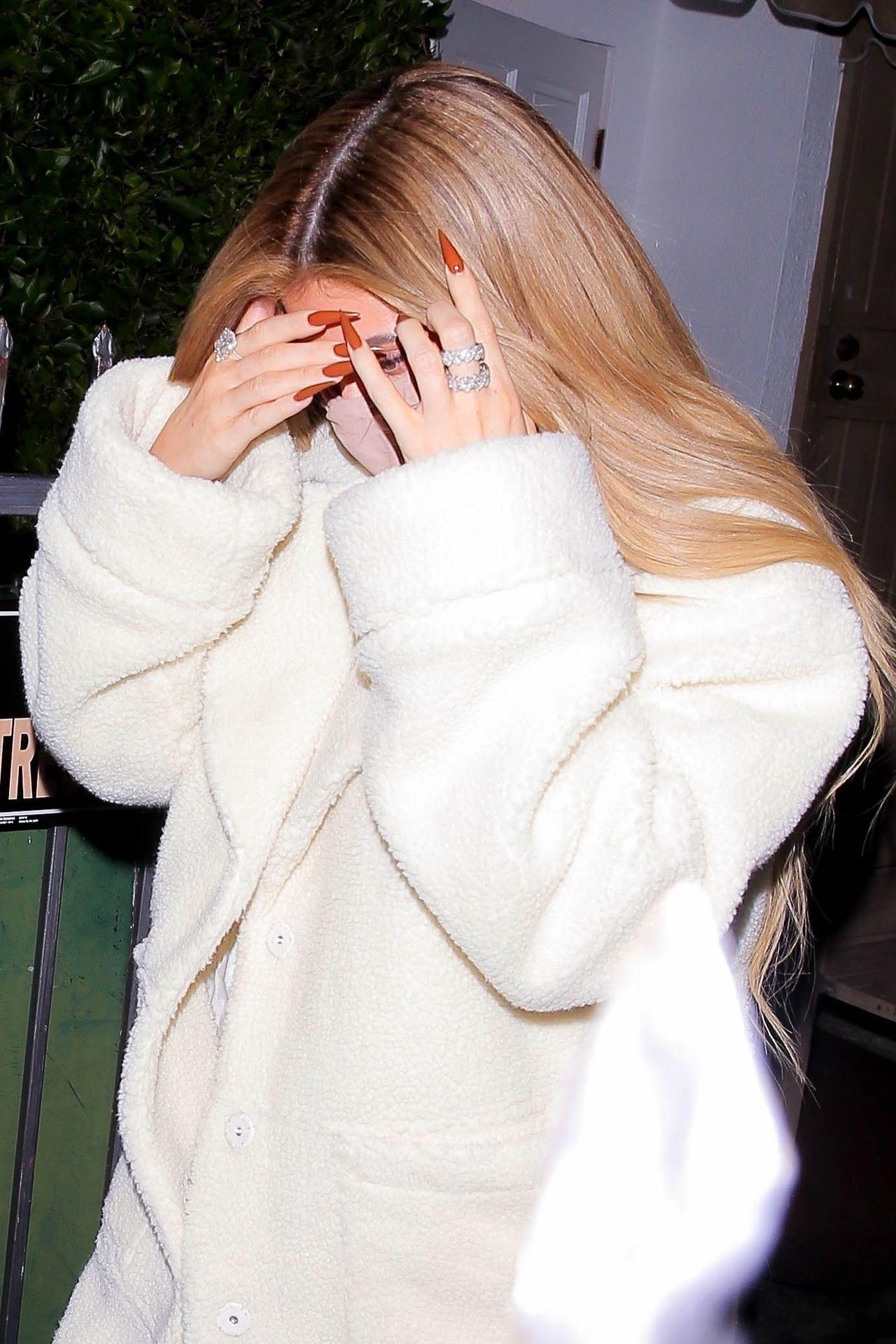 Kylie Jenner zakrywa twarz przed fotoreporterami.